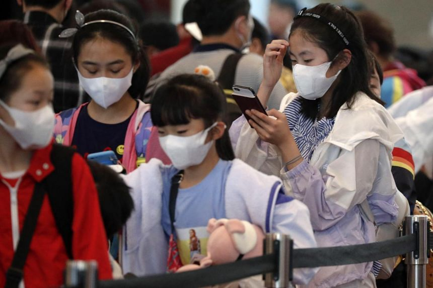 Children wearing protective masks queue at a check-in counter at the Changi Airport in Singapore, on Jan 23, 2020.
