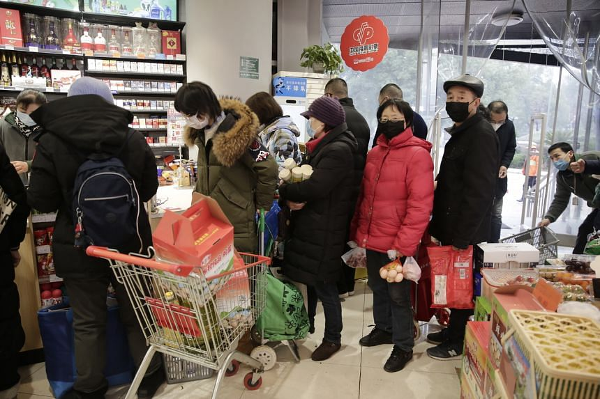 Residents queue up to buy groceries at a market as food prices soar due to the coronavirus outbreak in Wuhan City, on Jan 23, 2020.