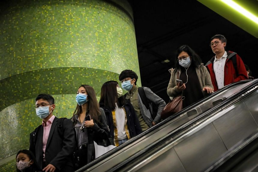 Commuters wearing face masks as a precautionary measure to protect against the possible spread of the new coronavirus at an MTR station in Hong Kong on Jan 23, 2020.