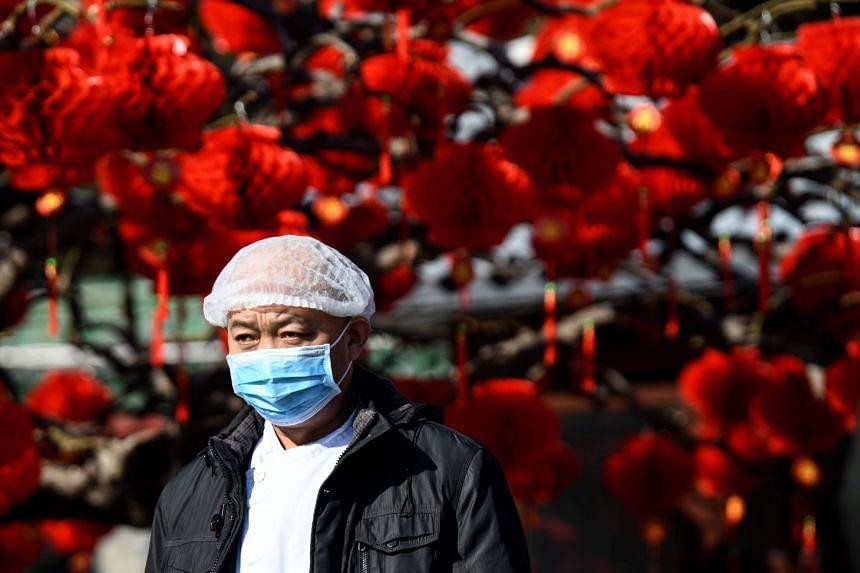 A man wearing a protective face mask walks along a street in Beijing on Jan 23, 2020.