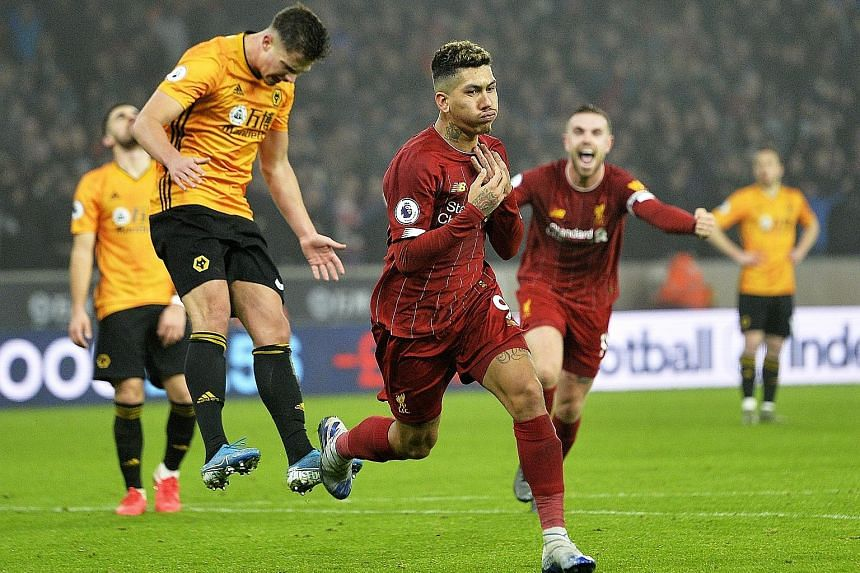 Liverpool's Roberto Firmino wheeling away to celebrate his late winner against Wolves, the Brazilian's 10th away goal in all competitions.
