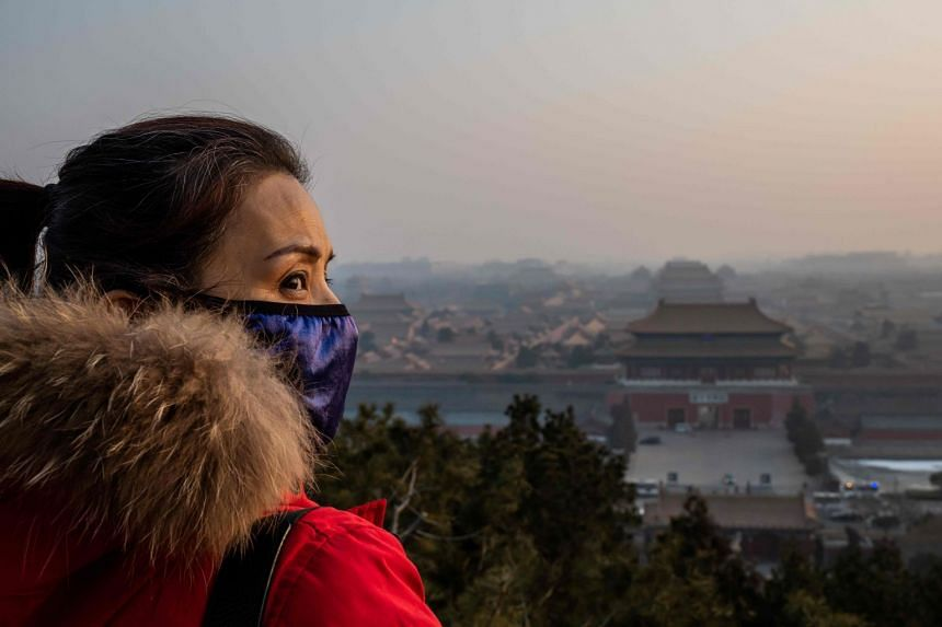 A woman wearing a protective face mask looks on at Jingshawn park overlooking the Forbidden City (right) in Beijing on Jan 25, 2020.