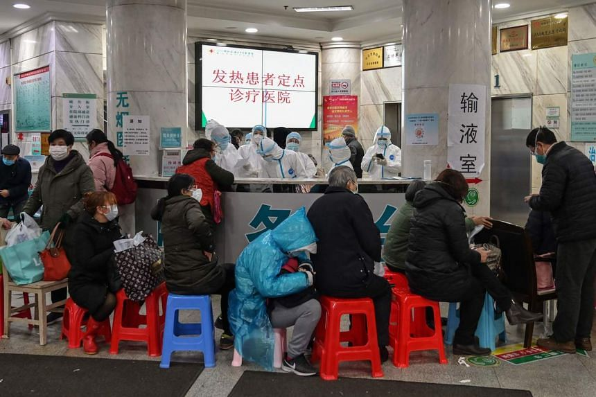People wait as medical staff (back) wear protective clothing to help stop the spread of a deadly virus which began in the city, at Wuhan Red Cross Hospital in Wuhan on Jan 24, 2020.