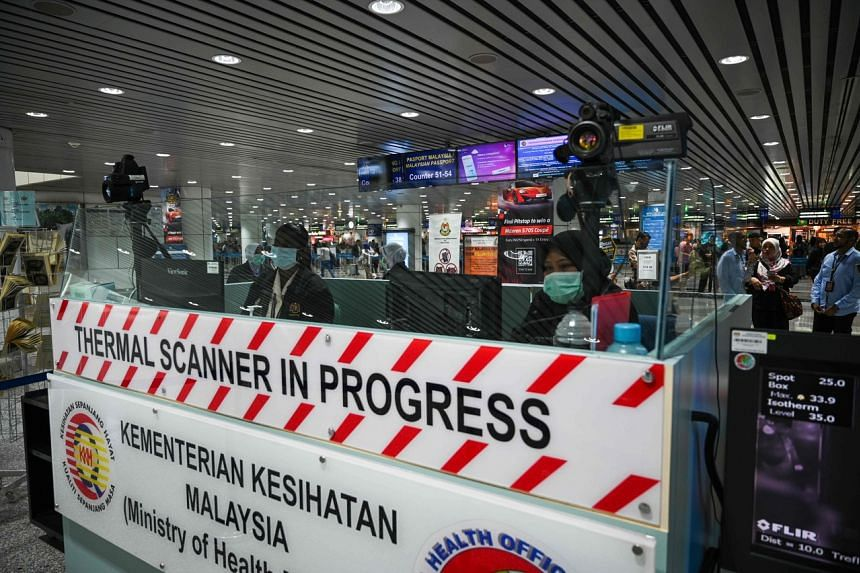 Malaysian health officers screen arriving passengers with thermal scanners at Kuala Lumpur International Airport, on Jan 21, 2020.