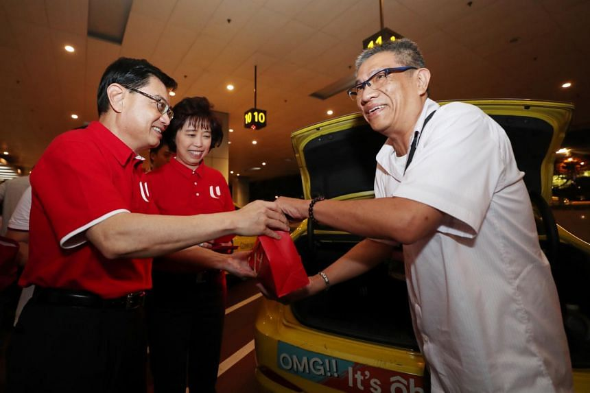 Deputy Prime Minister  Heng Swee Keat and NTUC President Mary Liew give out red packets to taxi drivers at Changi Airport Terminal 3 on Jan 25, 2020.