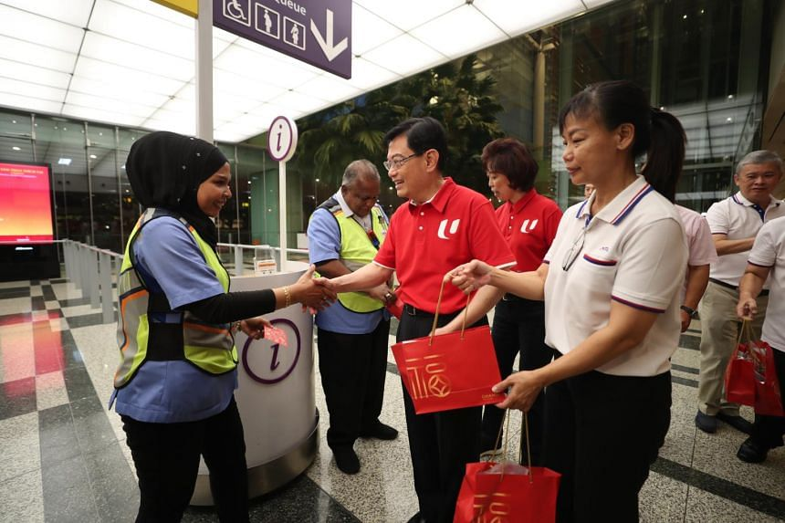 Deputy Prime Minister Heng Swee Keat (centre, in red) and NTUC President Mary Liew (right) give out red packets to airport staff at Changi Airport Terminal 3 on Jan 25, 2020.