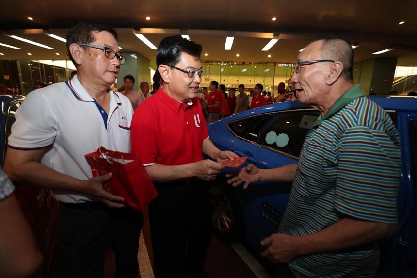 Deputy Prime Minister Heng Swee Keat (in red) gives out red packets to taxi drivers at Changi Airport Terminal 3 on Jan 25, 2020.