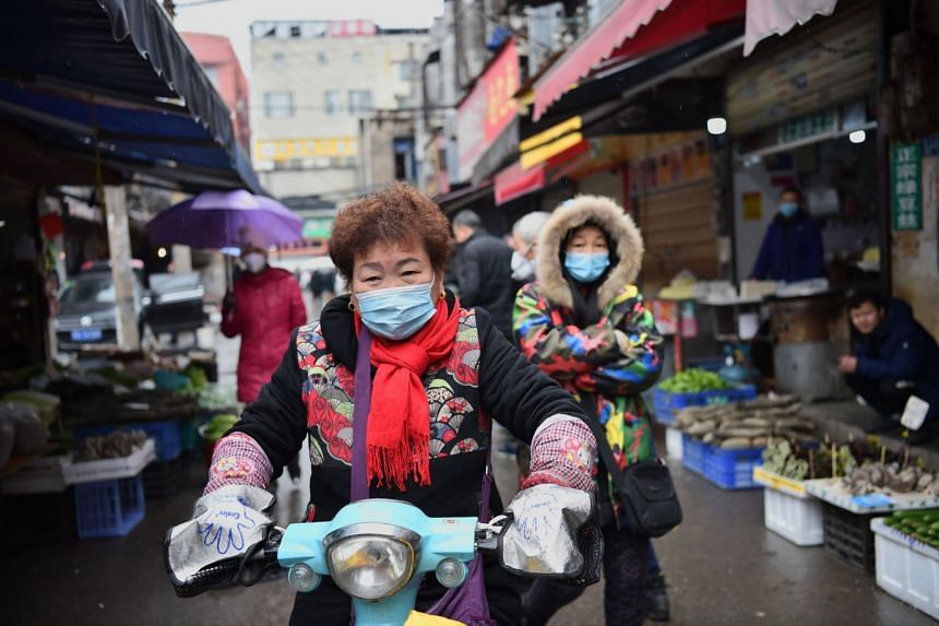 A woman wearing a mask rides her scooter through a market in Wuhan, on Jan 24, 2020.
