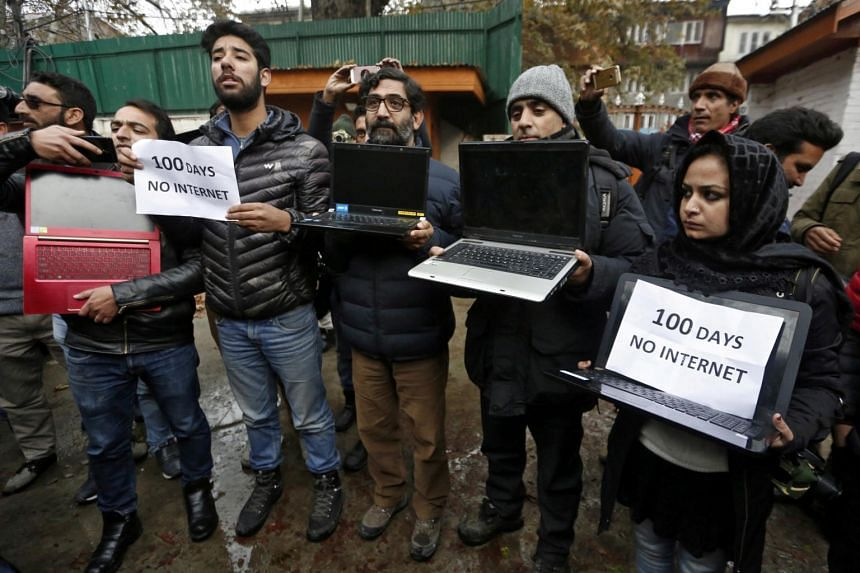 In a photo taken on Nov 12, 2019, Kashmiri journalists display laptops and placards during a protest demanding restoration of internet service, in Srinagar.