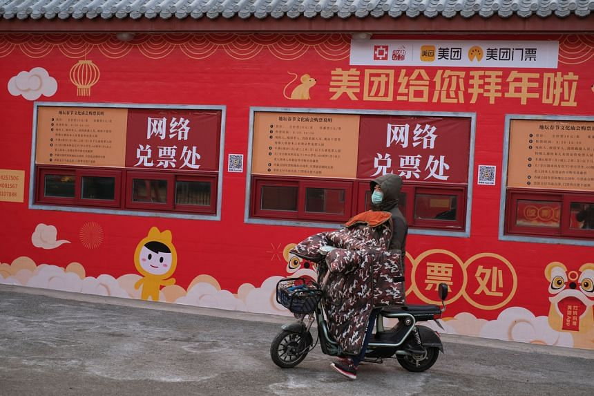 A man rides on his scooter in front of a closed ticket office for internet bookings after the temple fair for the Chinese Lunar New Year in Ditan Park was canceled in Beijing, China on Jan 24, 2020.