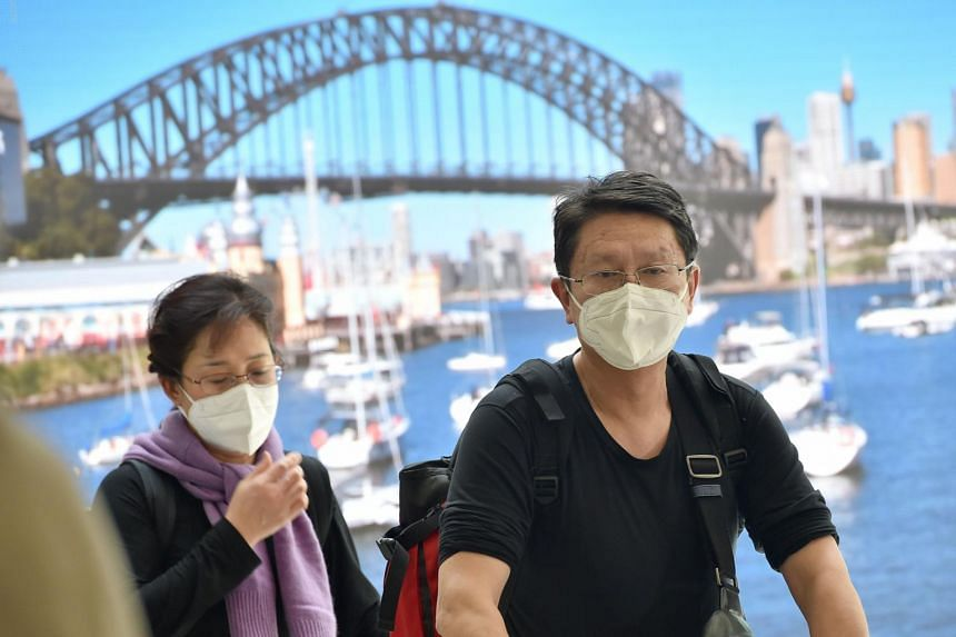Passangers wearing masks arrive at Sydney airport after landing on a plane from the Chinese city of Wuhan, on Jan 23, 2020.