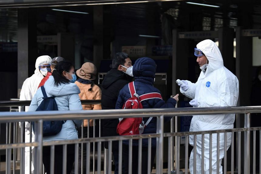 Commuters being checked by security personnel wearing hazardous material suits at the entrance to an underground train station in Beijing yesterday.