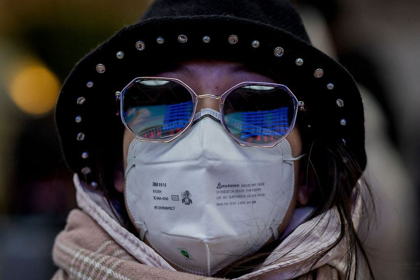 A passenger wearing a protective mask travels for the Chinese New Year holiday in Beijing on Jan 24, 2020.