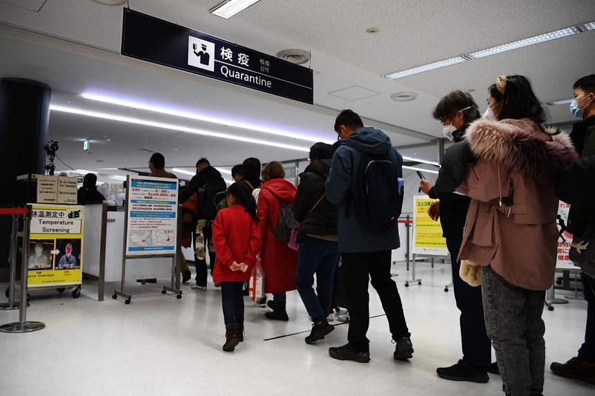 Passengers who arrived on one of the last flights from Wuhan, China, walk through a health screening station at Tokyo Narita airport on Jan 23, 2020.