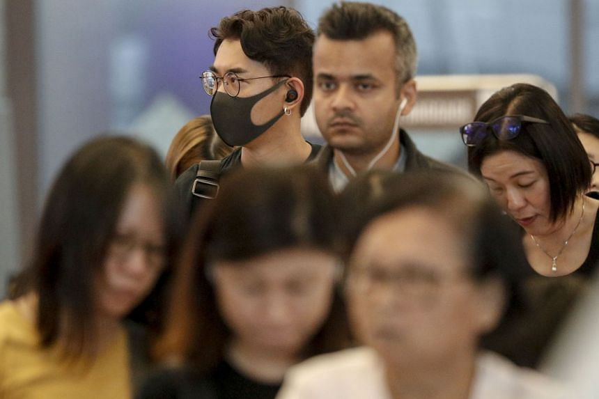 A tourist is seen wearing a mask while queuing at a check-in counter at Changi Airport in Singapore, Jan 23, 2019.
