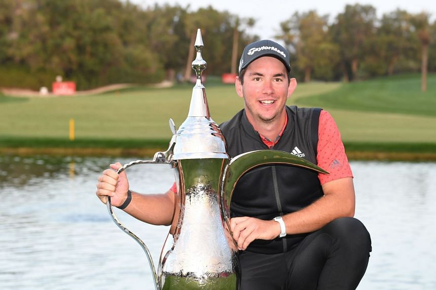 Lucas Herbert of Australia celebrating with the championship trophy after winning the play-offs in the final round of the Omega Dubai Desert Classic at the Emirates Golf Club in Dubai on Jan 26, 2020.