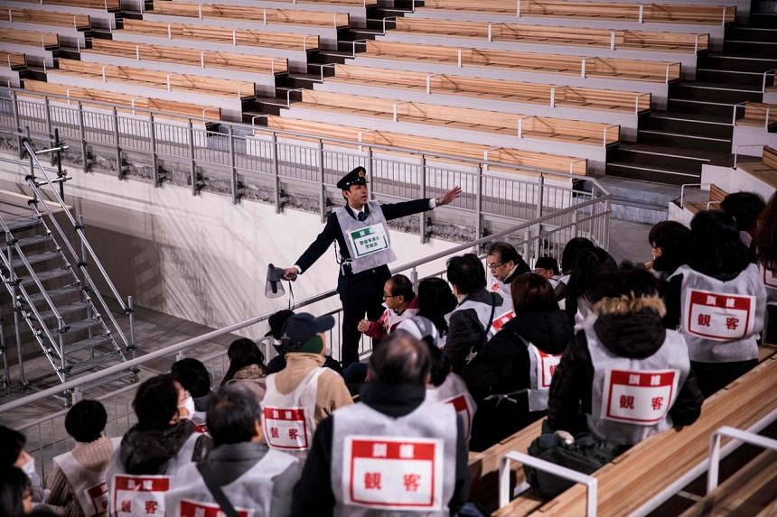 In a photo taken on Dec 19, 2019, a police officer guides spectators during a simulation disaster drill at the Ariake Gymnastics Centre, a venue for the Tokyo 2020 Olympic and Paralympic Games.