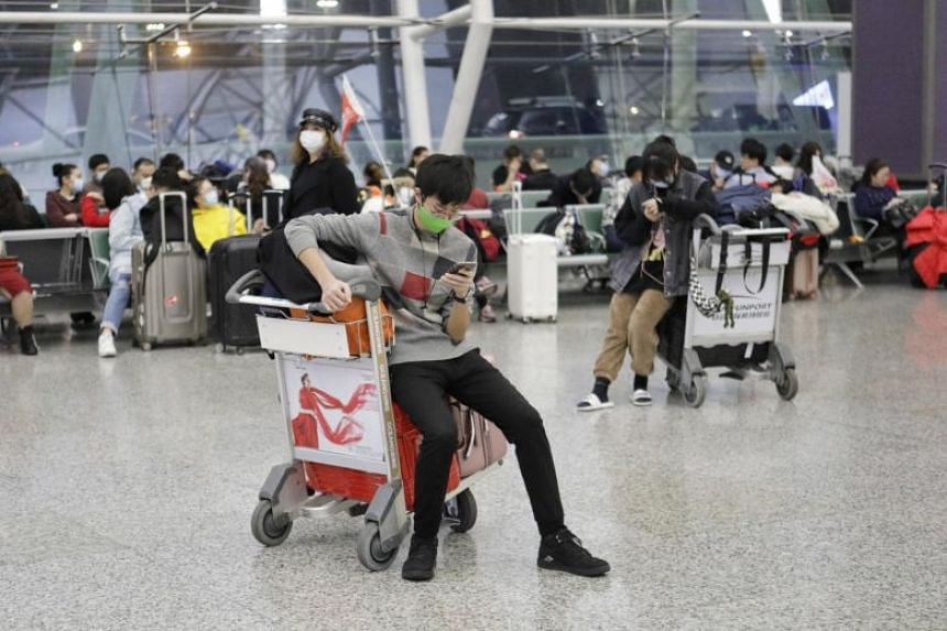 Passengers wear masks as they wait at Guangzhou airport, on Jan 23, 2020.