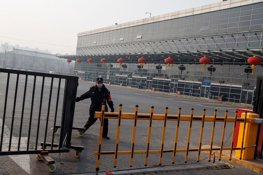A security guard closes a gate at the Sihui Long Distance Bus Station in Beijing after the city has stoped inter-province buses services, on Jan 26, 2020.