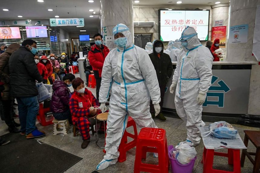 Medical staff members walk next to patients (left) waiting for medical attention at the Wuhan Red Cross Hospital in Wuhan, on Jan 25, 2020.