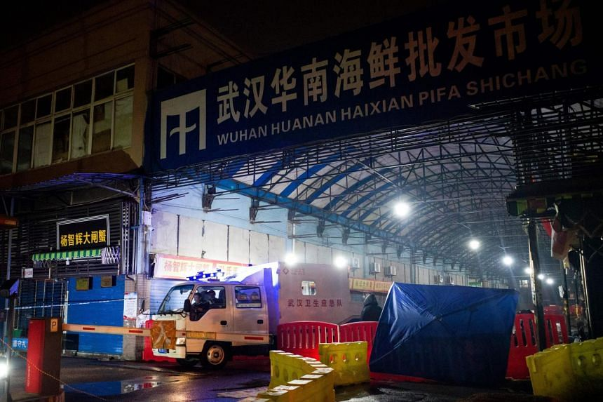 In a photo taken on Jan 11, 2020, members of the Wuhan Hygiene Emergency Response Team are seen leaving the closed Huanan Seafood Wholesale Market.