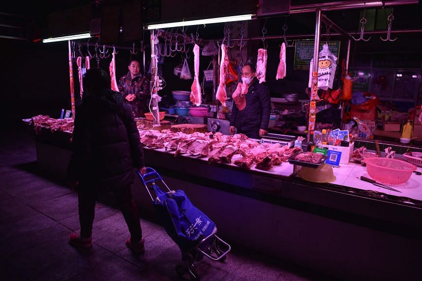 A seller is seen wearing a face mask at a market in Wuhan, China, on Jan 24, 2020.