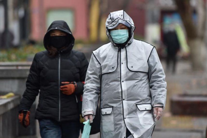 People wear protective facemasks as they walk by a hospital in Wuhan on Jan 26, 2020.