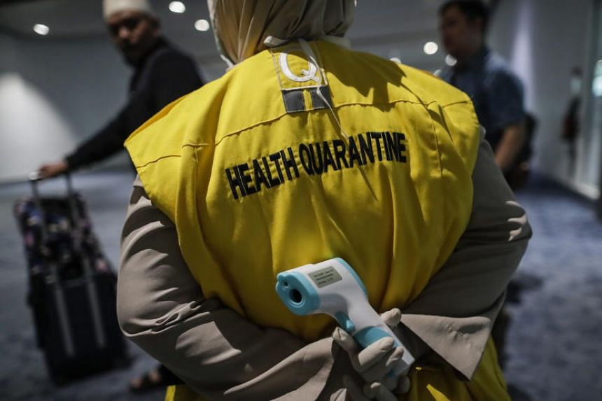 An Indonesian health quarantine official is seen holding a thermal scanner at Soekarno-Hatta International Airport in Tangerang, near Jakarta, on Jan 22, 2020.