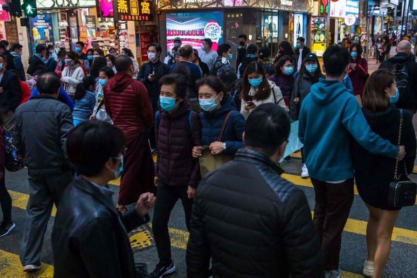 People wearing masks cross a street in Hong Kong on Jan 26, 2020.