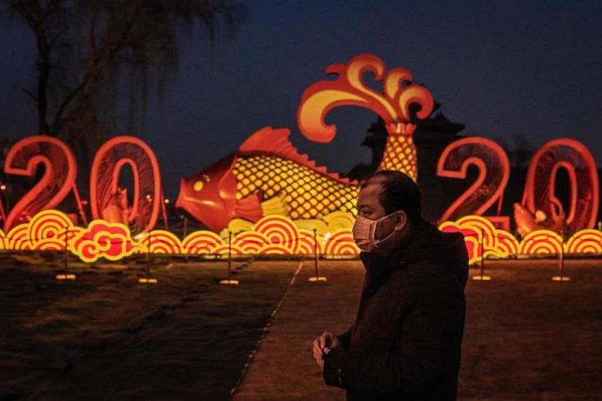 A man wears a protective face mask to help stop the spread of a deadly coronavirus which originated in the central city of Wuhan, as he walks on the outskirts of the Forbidden City, on Jan 25, 2020.