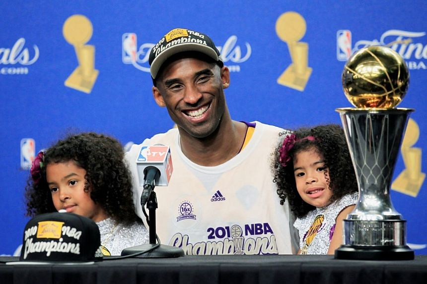 Kobe Bryant smiles with daughters Gianna and Natalia with the Bill Russell MVP Trophy after his team defeated the Boston Celtics in Game 7 to win the 2010 NBA Finals basketball series, on June 17, 2010 .