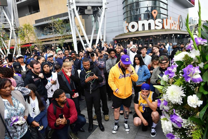 People gather around a makeshift memorial for former NBA and Los Angeles Lakers player Kobe Bryant after learning of his death at LA Live plaza in front of Staples Center in Los Angeles, on Jan 26, 2020.