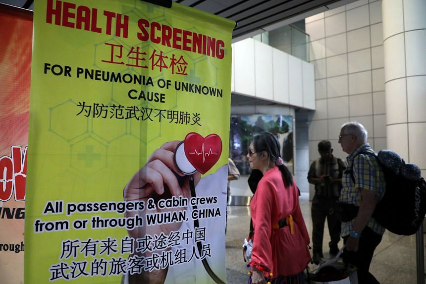 Passengers pass by a banner about the Wuhan virus at a thermal screening point at international arrival terminal of Kuala Lumpur International Airport, on Jan 21, 2020.