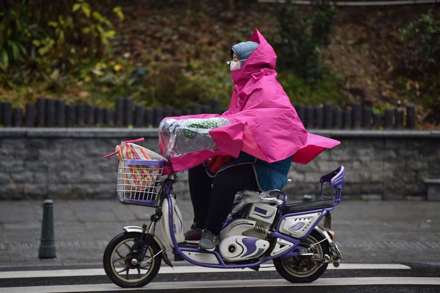 A woman wearing a face mask rides a scooter along a street in Wuhan, on Jan 26, 2020.
