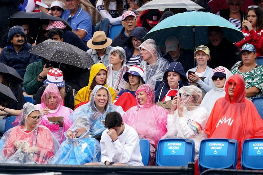 Spectators look on as rain falls during the Australian Open tennis tournament in Melbourne on Jan 20, 2020.  Temperatures in the city are forecast to reach 41 deg C later in the week.