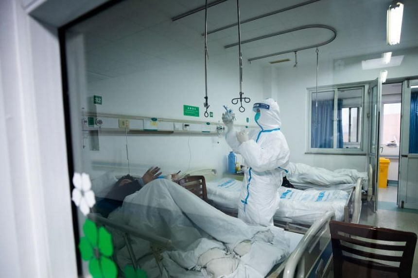 A medical worker treats a patient at Wuhan Jinyintan hospital in Wuhan, China, on Jan 26, 2020.