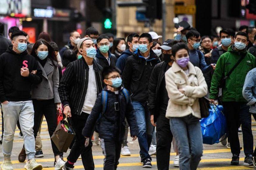 Pedestrians wearing face masks cross a road in Hong Kong on Jan 27, 2020.