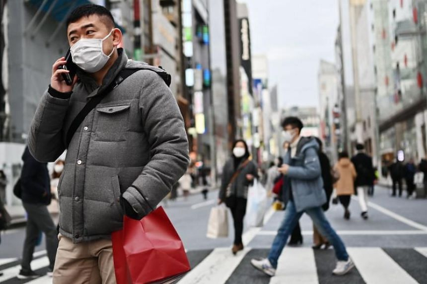 Pedestrians wear protective masks as they walk on a street in Tokyo's Ginza area on Jan 25, 2020.