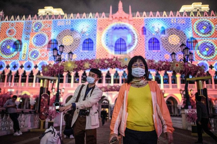 People are seen wearing masks outside a casino resort in Macau on Jan 22, 2020.