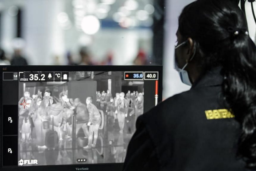 A health official checks passengers going through a thermal scanner upon their arrival at Kuala Lumpur International Airport on Jan 21, 2020.
