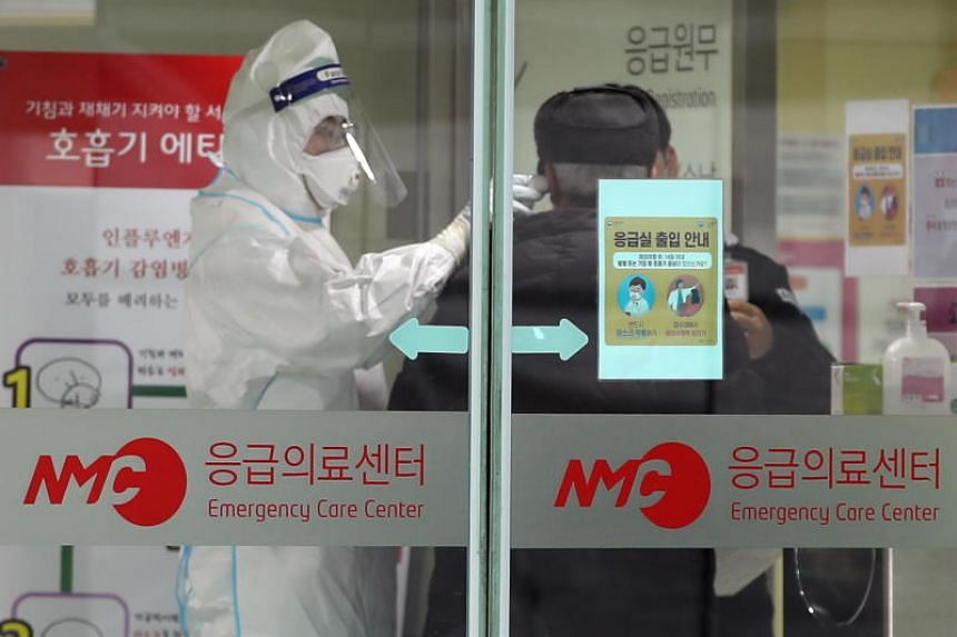 A medical official checks the temperature of a patient at a hospital in Seoul on Jan 27, 2020.