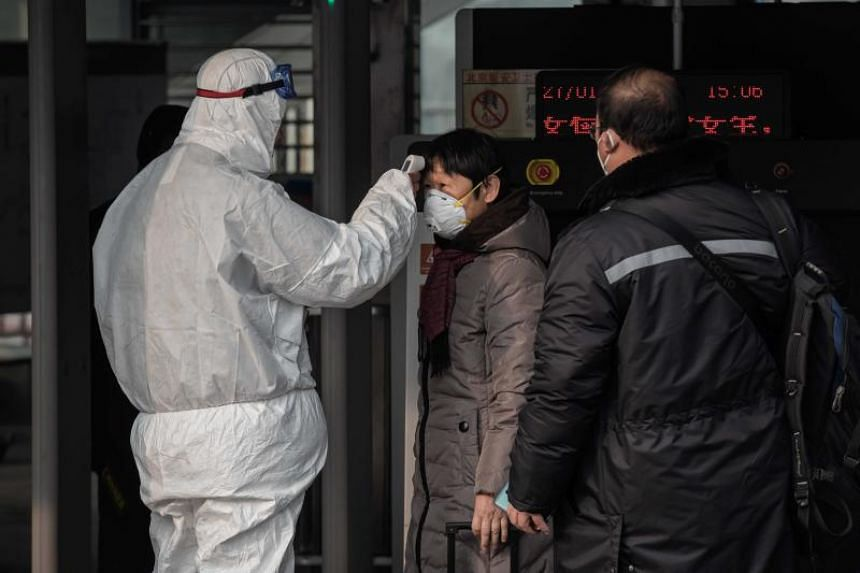 A security personnel wearing protective clothing checks the temperature of a woman at a subway station entrance in Beijing on Jan 27, 2020.