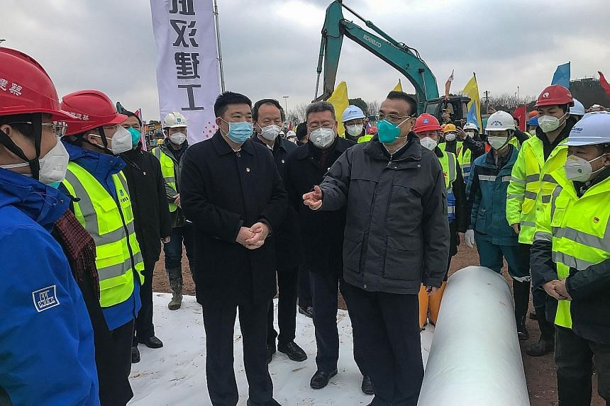 Chinese Premier Li Keqiang (centre) addressing workers at the construction site of a new hospital being built to treat patients of the novel coronavirus in Wuhan, capital of Hubei province, yesterday. During a visit to several sites in Wuhan yesterda