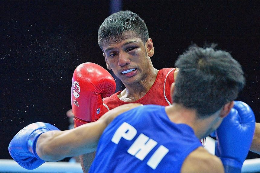 Philippines' Ian Clark Bautista (in blue) beating home favourite Mohamed Hanurdeen Hamid to win the men's flyweight boxing gold medal at the 2015 SEA Games in Singapore. ST FILE PHOTO