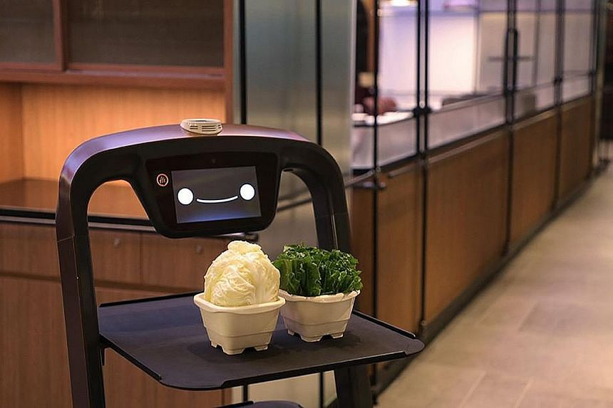 A robot server at Haidilao's Marina Square outlet carrying hotpot ingredients from the kitchen to tables - a task that can be done within minutes.