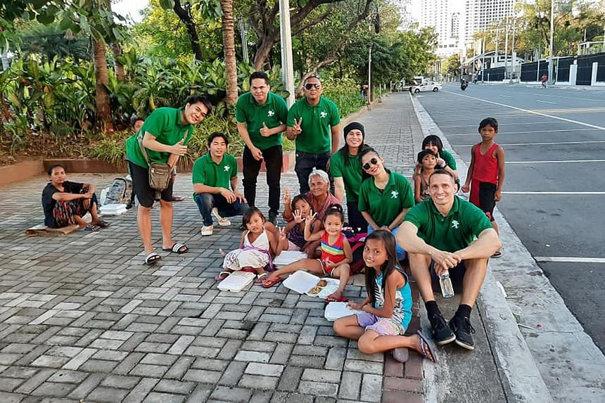 Volunteers from the Robin Hood Army serving food to poor children in Bangalore (above) and to the homeless in the Philippines (below). The Indian non-profit has a zero-funds approach and is volunteer-driven. PHOTOS: ROBIN HOOD ARMY