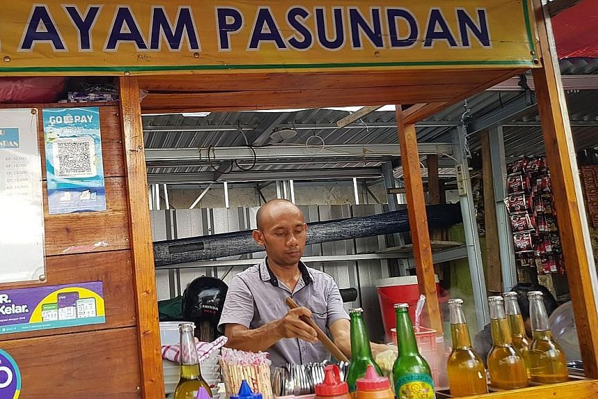 A noodle street vendor in Indonesia that accepts payment from e-wallets Go-Pay and Ovo. At least 39 e-wallet apps have been licensed by the central bank. The total value of transactions made through e-wallets was US$1.5 billion (S$2 billion) in 2018,