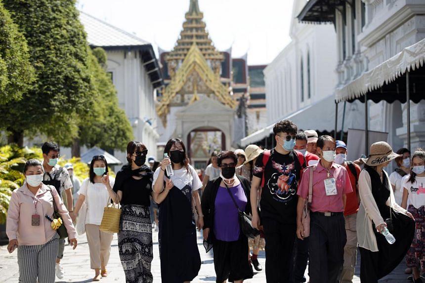 Tourists wearing masks visiting the Grand Palace in Bangkok, Thailand, on Jan 27, 2020.