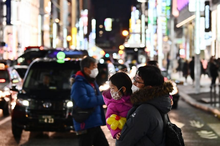 Pedestrians wearing masks to help stop the spread of a deadly virus which began in the Chinese city of Wuhan, walk on a street in Tokyo's Ginza area, on Jan 26, 2020.