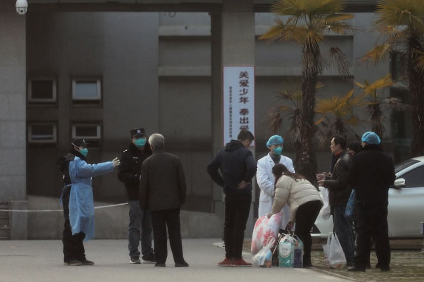 Medical staff and security personnel stop patients' family members from being too close to the Jinyintan hospital, where the patients with pneumonia caused by the new strain of coronavirus are being treated, in Wuhan, on Jan 20, 2020.